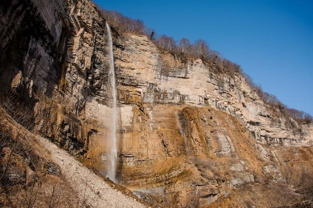 Cienki wodospad strumień spływający z wysokiej skały w kanionie martvili na jesienny dzień
