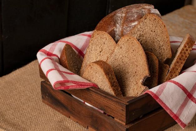 Cienkie kromki chleba w drewnianym koszu.