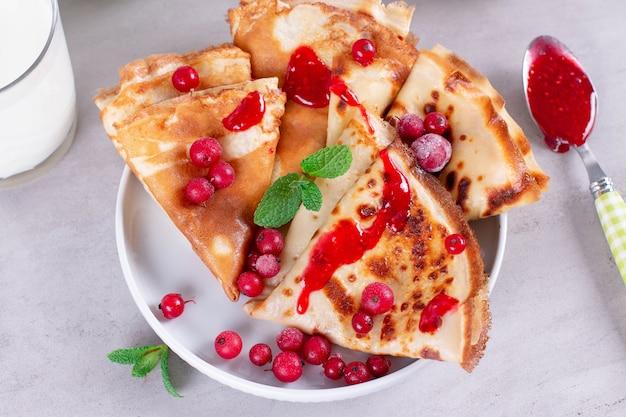 Cienkie naleśniki lub naleśniki na talerzu z dżemem i mrożonymi jagodami, mięta. tradycyjne śniadanie lub deser.