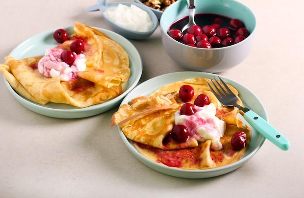 Cienkie naleśniki z jogurtem i wiśnią, podawane