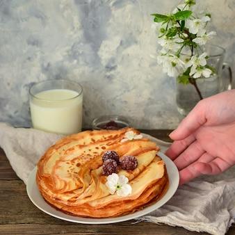 Cienkie naleśniki z wiśniami. naleśniki w białym talerzu. powierzchnia drewna. talerz z jedzeniem w rękach.