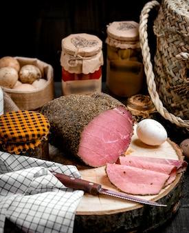 Cienkie plasterki mięsa jagnięcego na drewnianej pianie