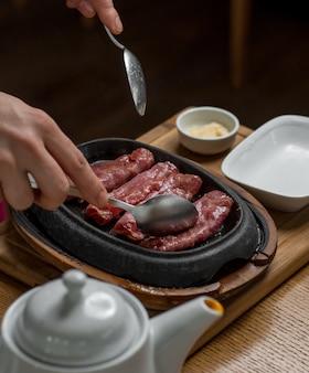 Cienkie smażone zawijane mięso wołowe w owalnej żeliwnej patelni