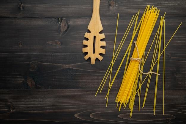 Cienkie spaghetti na czarnym drewnianym tle.