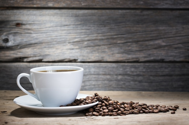 Ciepła filiżanka kawy na drewnianym tle