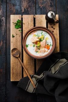 Ciepła fińska kremowa zupa z łososiem i warzywami w starej ceramicznej misce na starej drewnianej powierzchni. styl rustykalny. widok z góry.
