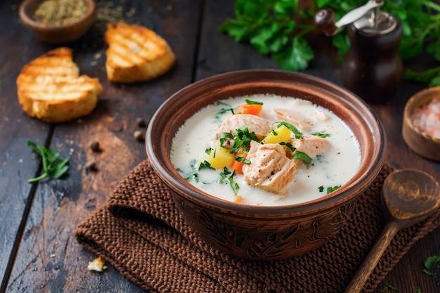 Ciepła fińska kremowa zupa z łososiem i warzywami w starej ceramicznej misce na starej drewnianej powierzchni. styl rustykalny.