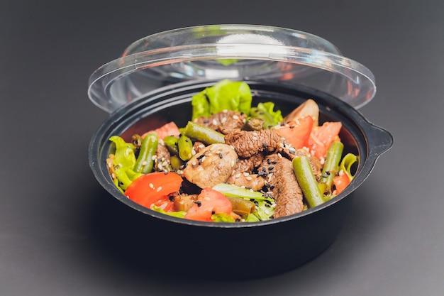 Ciepła sałata z wątróbką drobiową, smażonymi grzybami, oliwą, przyprawami i balsamem. wyśmienita kolacja dla smakoszy. selektywna ostrość.