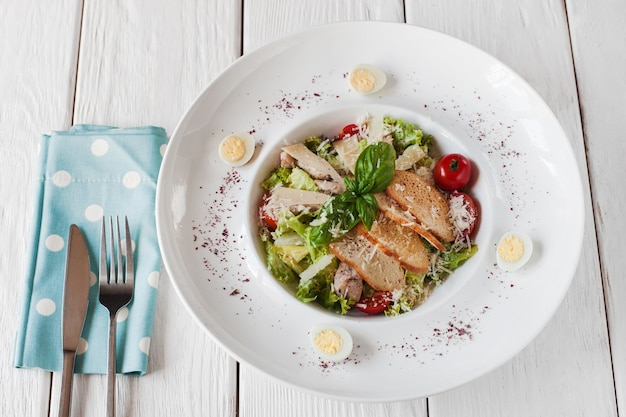 Ciepła sałatka z kurczakiem i grzankami na białym drewnianym stole