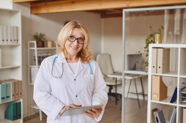 Ciepła talia w górę portret dojrzałej kobiety uśmiecha się do kamery i trzyma schowek podczas pracy w nowoczesnej klinice, kopia przestrzeń