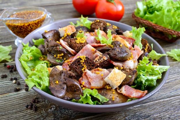 Ciepła zdrowa sałatka z wątróbki drobiowej, grzankami żytnimi, wędzonym boczkiem, zieloną sałatą i sosem musztardowym w misce o