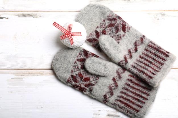 Ciepłe boże narodzenie. rękawiczki z dzianiny i zabawka na choinkę. tło wakacje nowy rok