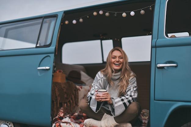 Ciepłe i przytulne. atrakcyjna młoda uśmiechnięta kobieta trzymająca kubek i odwracająca wzrok, siedząc wewnątrz niebieskiego mini vana w stylu retro