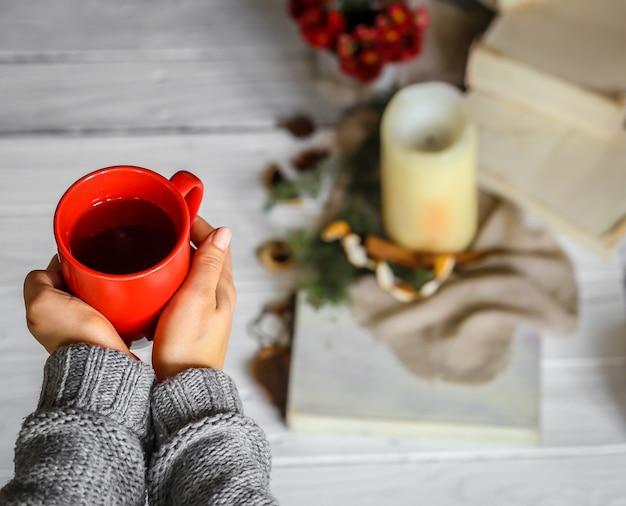 Ciepłe i przytulne, ręce dziewczyny koncepcja z filiżanką herbaty