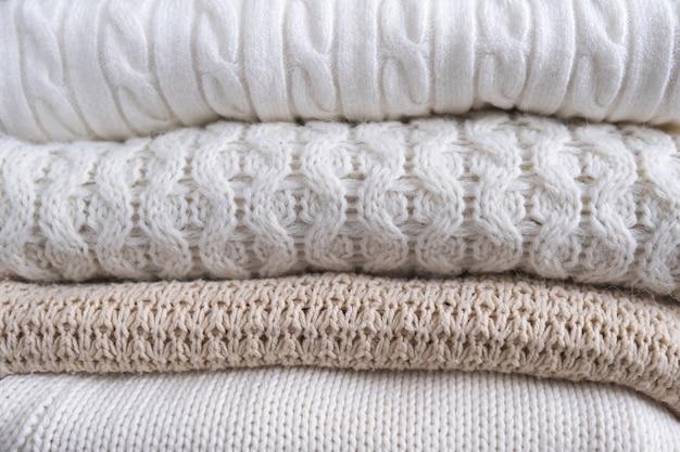 Ciepłe, przytulne ubrania z różnymi wzorami dzianin z bliska. tło jesień lub zima.