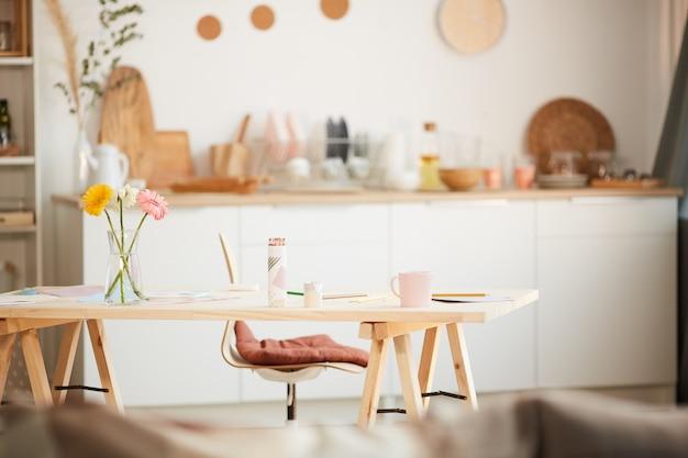 Ciepłe, stonowane wnętrze domu z przytulną drewnianą kuchnią i kwiatami na stole, miejsce na kopię