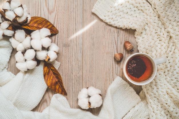 Ciepłe swetry i filiżanka herbaty. przytulna martwa natura w ciepłych odcieniach. koncepcja jesień zima.