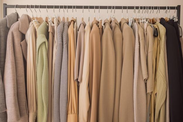 Ciepłe swetry z pastelowej dzianiny na białych wieszakach.