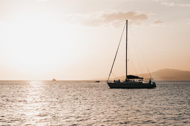 Ciepłe światło czerwonawo-pomarańczowe kolory słońca w pobliżu morza łodzią