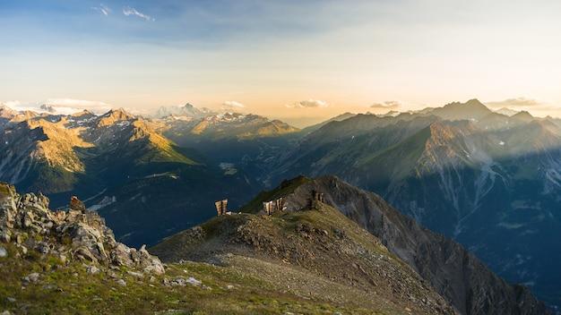 Ciepłe światło o wschodzie słońca na szczytach górskich, grzbietach i dolinach