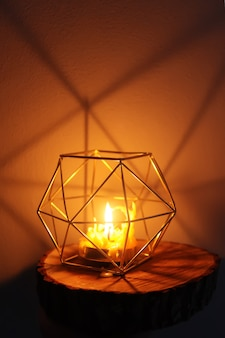 Ciepłe światło ręcznie wykonanej świecy z naturalnego wosku pszczelego w świeczniku na drewnianym plastrze.