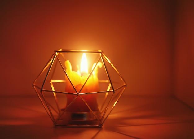 Ciepłe światło ręcznie wykonanej świecy z naturalnego wosku pszczelego w świeczniku na drewnianym plastrze