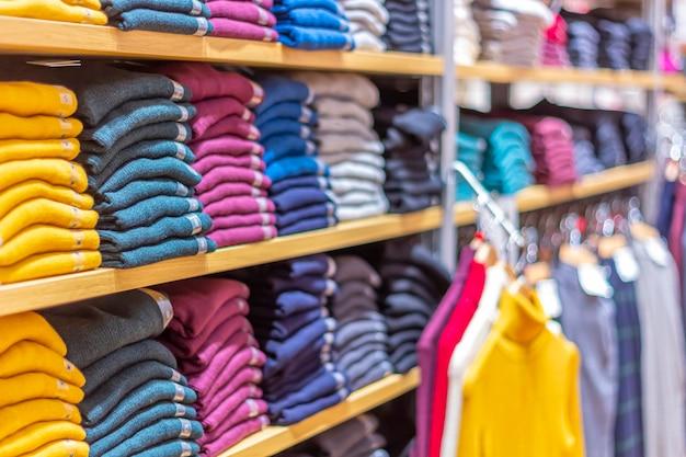 Ciepłe ubranie starannie złożone na półce. szereg kolorowych swetrów, swetrów, bluz, swetrów, bluz z kapturem w salonie lub sklepie.
