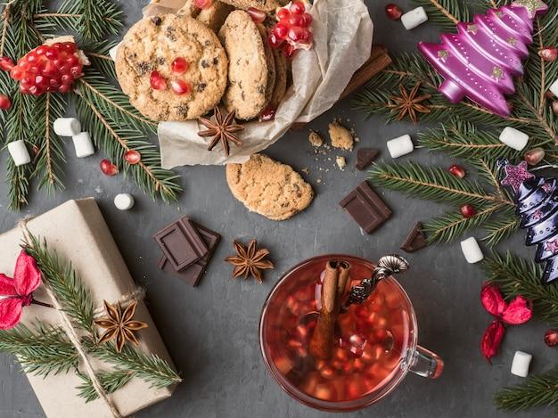 Ciepłe wino w kubku pudełko ciasteczka z czekoladowymi dekoracjami świątecznymi