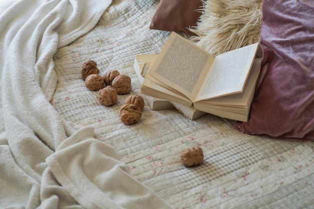Ciepłe wnętrze salonu z otwartą książką z orzechami włoskimi. czytaj, odpoczywaj. koncepcja zimowego weekendu. przytulna koncepcja jesień lub zima.