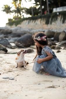 Ciepłe zdjęcie uroczego psa i preteen dziewczyny w sukience z wieńcem bawią się na wybrzeżu w tajlandii.