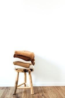Ciepłe zimowe damskie wełniane swetry z dzianiny, swetry układają się na drewnianym stołku w kolorze białym. kobiece nowoczesne ubrania moda blog koncepcja.