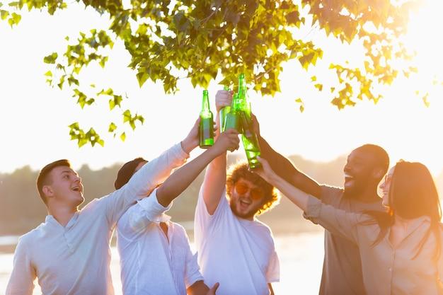 Ciepły. grupa przyjaciół brzęk butelek piwa podczas pikniku na plaży w promieniach słońca. styl życia, przyjaźń, zabawa, weekend i odpoczynek. wygląda wesoło, wesoło, świętująco, odświętnie.