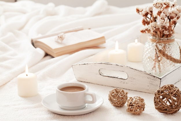 Ciepły i domowy skandynawski hygge z filiżanką kawy, otwartą książką i tacą w stylu retro z płonącymi świecami.
