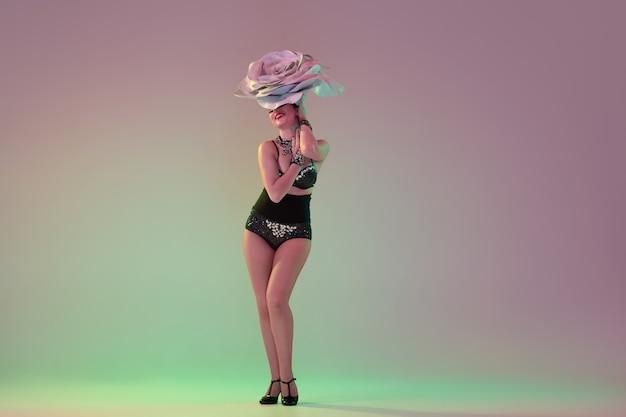 Ciepły i lśniący. młoda tancerka z ogromnymi kwiatowymi kapeluszami w neonowym świetle na ścianie gradientowej.
