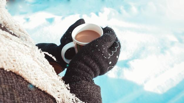 Ciepły kubek gorącej kawy rozgrzewającej w dłoniach w rękawiczkach. kobiece ręce na śniegu, zima