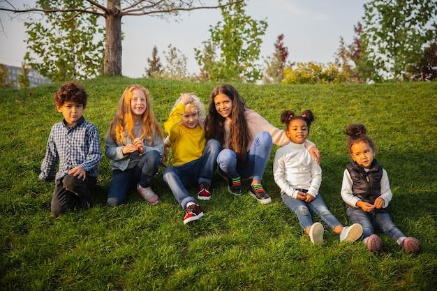 Ciepły. międzyrasowa grupa dzieci, dziewcząt i chłopców grających razem w parku w letni dzień. przyjaźń nie ma rasy. szczęście, dzieciństwo, edukacja, koncepcja różnorodności. wyglądaj na szczęśliwego i szczerego.