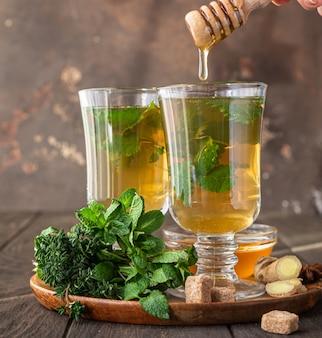 Ciepły napar z ziół w szklankach na chłodne dni. dwie filiżanki herbaty imbirowej z miętą, tymiankiem i miodem.