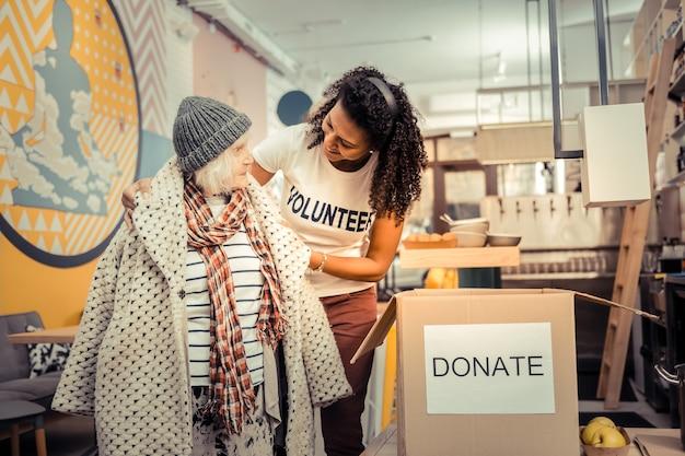 Ciepły płaszcz. radosna, przyjazna kobieta uśmiecha się, pomagając biednej kobiecie założyć płaszcz