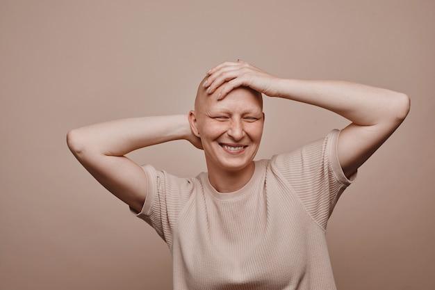 Ciepły portret beztroskiej łysej kobiety dotykającej ogolonej głowy i uśmiechającej się, pozując na minimalnym beżowym tle w studio, łysienie i świadomość raka, kopia przestrzeń