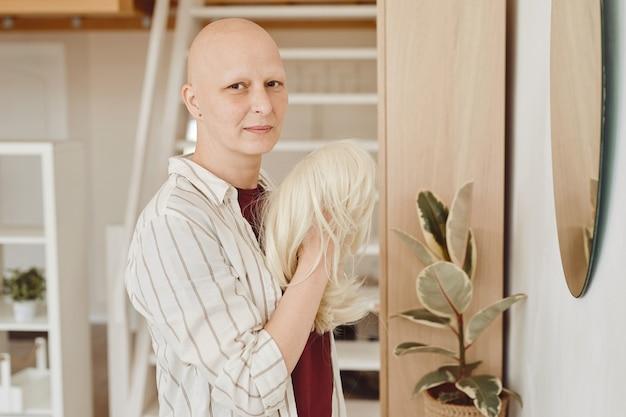 Ciepły portret łysej dorosłej kobiety patrząc na kamerę trzymającą perukę stojąc przy lustrze w nowoczesnym wnętrzu domu, łysieniu i świadomości raka, skopiuj przestrzeń