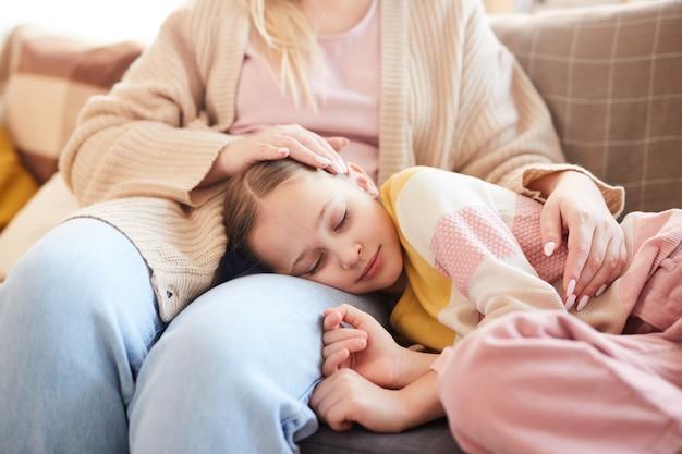 Ciepły portret śliczna dziewczyna śpi na kolanach matki, leżąc na kanapie w domu, kopia przestrzeń