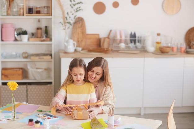 Ciepły portret szczęśliwej matki przytulającej córkę podczas otwierania prezentów przy drewnianym kuchennym stole, kopia przestrzeń