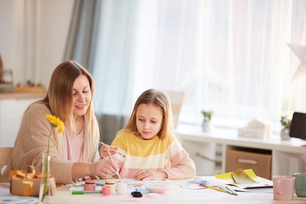 Ciepły portret uśmiechniętej dojrzałej matki malującej obrazki z uroczą córeczką siedząc przy drewnianym stole w przytulnym wnętrzu domu, miejsce na kopię