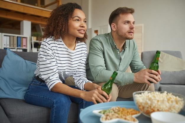 Ciepły portret współczesnej pary mieszanej oglądającej telewizję w domu i pijącej piwo, siedząc na kanapie w przytulnym mieszkaniu