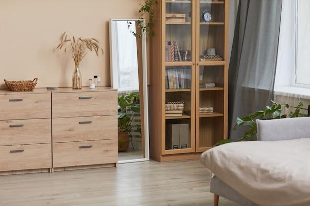 Ciepły, stonowany obraz tła minimalnego wnętrza sypialni z drewnianymi elementami i naturalnym wystrojem, skopiuj przestrzeń