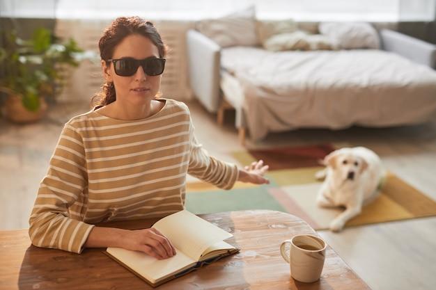 Ciepły, stonowany portret nowoczesnej niewidomej kobiety czytającej książkę brajlowską siedząc przy stole w przytulnym wnętrzu domu i sięgającej po psa przewodnika, miejsce kopiowania