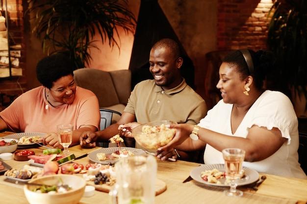 Ciepły, stonowany portret szczęśliwej afrykańskiej rodziny siedzącej przy stole na zewnątrz i delektującej się kolacją...