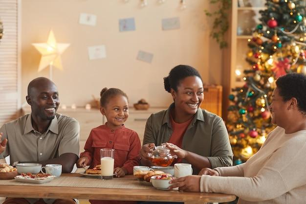 Ciepły, stonowany portret szczęśliwej rodziny afroamerykańskiej, cieszącej się herbatą i przekąskami podczas świętowania bożego narodzenia w domu w przytulnym wnętrzu