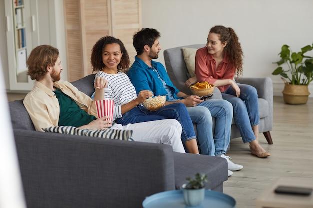 Ciepły, stonowany portret wieloetnicznej grupy przyjaciół, którzy razem oglądają telewizję, siedząc na wygodnej kanapie w domu i delektując się przekąskami