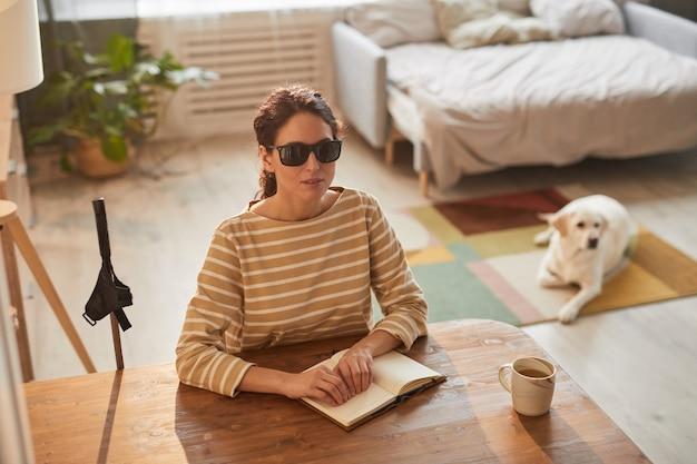Ciepły, stonowany, wysoki kąt portret nowoczesnej niewidomej kobiety czytającej książkę braille'a siedząc przy stole w przytulnym wnętrzu domu z psem przewodnikiem w tle, miejsce na kopię